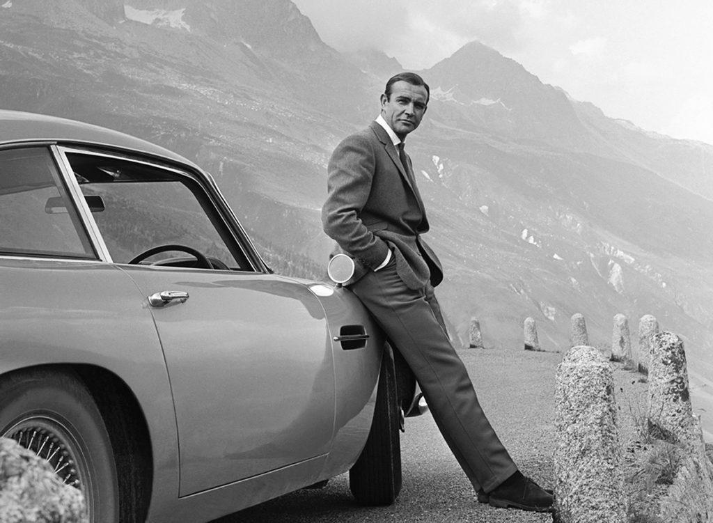 James bond leaning against car